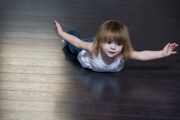 Little girl lying on floor and doing exercises